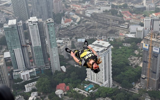 A BASE jumper leaps from Kuala Lumpur Tower on a hazy day during International Jump Malaysia 2019 in Kuala Lumpur, Malaysia, September 26, 2019. (Photo by Chong Voon Chung/Xinhua News Agency/Barcroft Media)