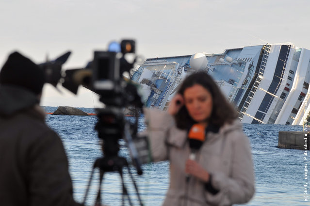 A journalist is seen in feont of the cruise ship Costa Concordia that  lies stricken off the shore of the island of Giglio