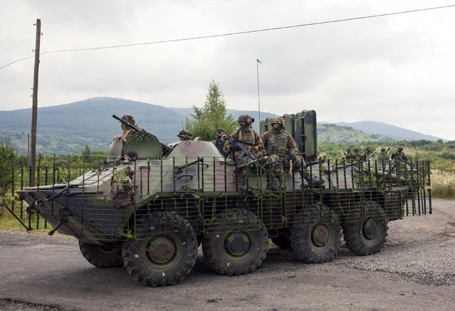 Ukrainian government servicemen ride on top of an armoured personnel carrier (APC) during search for members of Right Sector in the village of Bobovyshche near Mukacheve, Ukraine, July 13, 2015. (Photo by Reuters/Stringer)