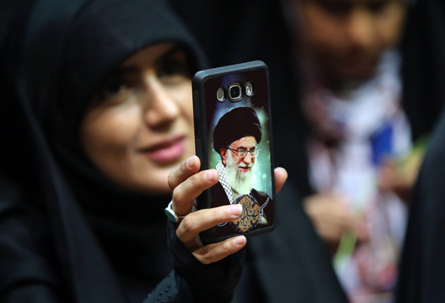 An Iranian woman shows her phone cover of Iran's Supreme Leader Ayatollah Ali Khamenei  as she attends a rally to support headscarves at the Sahhid Shiroudi Stadium in Tehran, on July 11, 2019. (Photo by AFP Photo/Stringer)