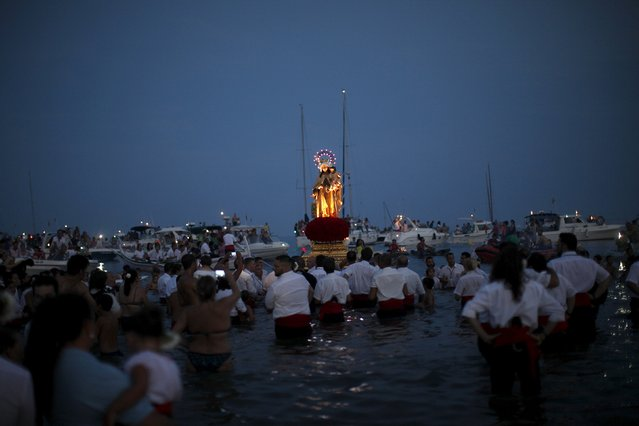 Men in traditional costumes carry a statue of the El Carmen Virgin into the sea during a procession in Malaga July 16, 2015. (Photo by Jon Nazca/Reuters)
