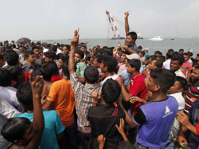 People protest against rescue workers involved in what the protesters claim is a slow rescue process for victims of the capsized M.V. Miraj-4 ferry, by the Meghna river at Rasulpur in Munshiganj district. (Photo by Reuters/Stringer)