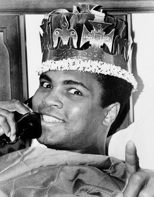 Muhammad Ali, in a jovial mood as his March 8 bout with Joe Frazier draws near, is seen speaking on the phone and wearing a king's crown, March 6, 1971, in Miami Beach. Ali and Frazier will meet on the 8th in New York's Madison Square Garden. (Photo by Joe Migon/AP Photo)