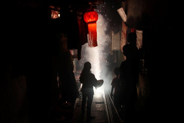 People watch as firecrackers burn on a street during Diwali, the Hindu festival of lights, in Mumbai, India, October 27, 2019. (Photo by Francis Mascarenhas/Reuters)
