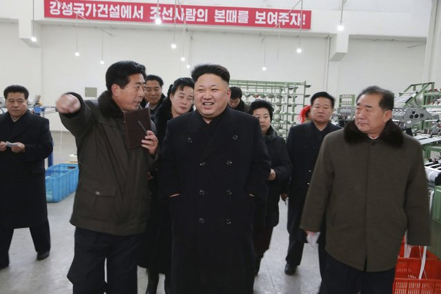 North Korean leader Kim Jong Un (front C) smiles as he gives field guidance at the Kim Jong Suk Pyongyang Textile Mill in this undated photo released by North Korea's Korean Central News Agency (KCNA) in Pyongyang December 20, 2014. (Photo by Reuters/KCNA)