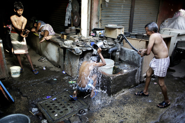 Indian migrant daily wage workers bath at a public tube well on a hot morning in New Delhi, India, Tuesday, May 17, 2016. (Photo by Altaf Qadri/AP Photo)