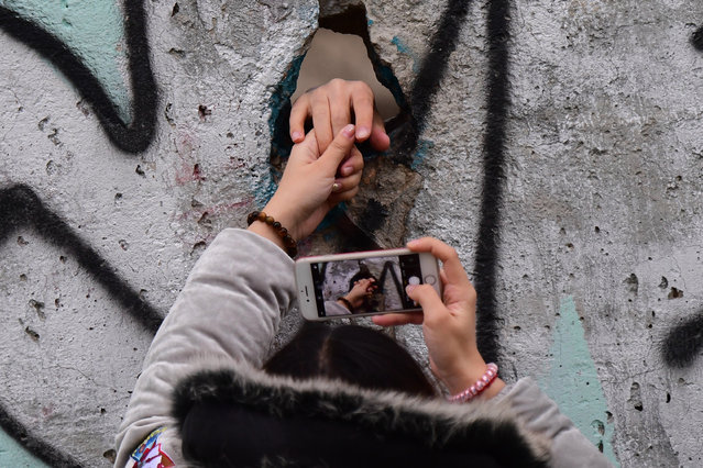 A visitor sticks a hand through a hole of the wall for a photograph, after the end of the official celebrations of the 30th anniversary of the fall of the Berlin Wall at the Berlin Wall Memorial site along Bernauer street in Berlin, Germany, 09 November 2019. The fall of the Berlin Wall led to the collapse of the communist East German GDR government in 1989 and the eventual reunification of East and West Germany. (Photo by Clemens Bilan/EPA/EFE)