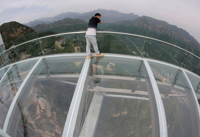 A man views a landscape on the glass sightseeing platform on Shilin Gorge in Beijing, China, May 27, 2016. (Photo by Kim Kyung-Hoon/Reuters)