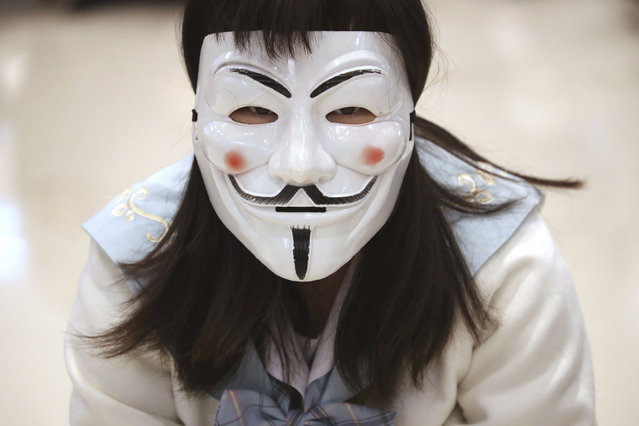 A protester wears a Guy Fawkes mask during a sit-in at a shopping mall to commemorate the four-month anniversary of an assault on commuters and protesters by armed men at a nearby train station in Hong Kong, Thursday, November 21, 2019. (Photo by Ng Han Guan/AP Photo)