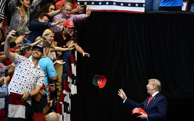 "US President Donald Trump throughs MAGA caps to supporters as he arrives for a ""Keep America Great"" campaign rally at the BB&T Center in Sunrise, Florida on November 26, 2019. (Photo by Mandel Ngan/AFP Photo)"