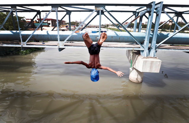 A boy jumps from a water pipe into a canal as temperatures soar in New Delhi, India, June 6, 2017. (Photo by Cathal McNaughton/Reuters)
