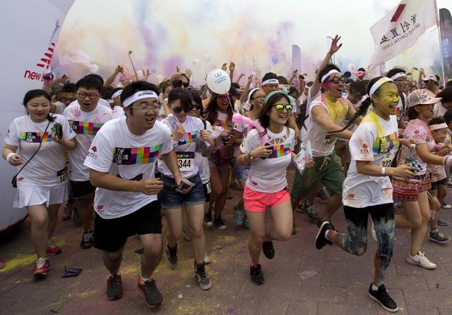 Color Run participants wave and throw colored powder during a five-kilometer run in Beijing, China Saturday, June 21, 2014. (Photo by Andy Wong/AP Photo)
