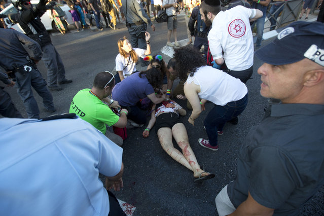 Paramedics help a wounded woman after an ultra-Orthodox Jew attacked people with a knife during a Gay Pride parade Thursday, July 30, 2015 in central Jerusalem. (Photo by Sebastian Scheiner/AP Photo)