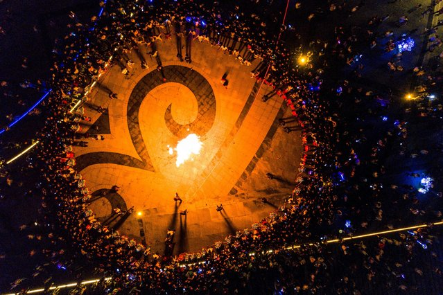 This aerial photo taken on July 29, 2019 shows people gathering around a bonfire as they celebrate the torch festival in Bijie, China's southwestern Guizhou province. (Photo by AFP Photo/China Stringer Network)