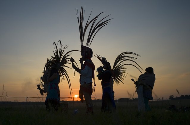 Revellers dressed in Aztec costume celebrate the summer solstice on Salisbury Plain in southern England June 21, 2014. Stonehenge is a celebrated venue of festivities during the summer solstice – the longest day of the year in the northern hemisphere – and it attracts thousands of revellers, spiritualists and tourists. Druids, a pagan religious order dating back to Celtic Britain, believe Stonehenge was a centre of spiritualism more than 2,000 years ago. (Photo by Kieran Doherty/Reuters)