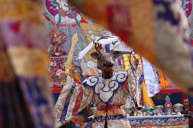 Elaborately dressed monks perform ceremonial dances costumed as animals during the Tenchi Festival on May 26, 2014 in Lo Manthang, Nepal. The Tenchi Festival takes place annually in Lo Manthang, the capital of Upper Mustang and the former Tibetan Kingdom of Lo. Each spring, monks perform ceremonies, rites, and dances during the Tenchi Festival to dispel evils and demons from the former kingdom. (Photo by Taylor Weidman/Getty Images)