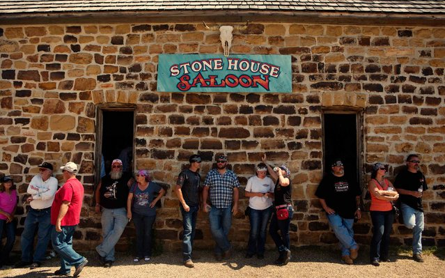 Rallygoers watch bikes pull up to the Stone House Saloon outside of Belle Fourche, South Dakota, while participating in the annual Sturgis Motorcycle Rally in South Dakota, August 5, 2015. (Photo by Kristina Barker/Reuters)