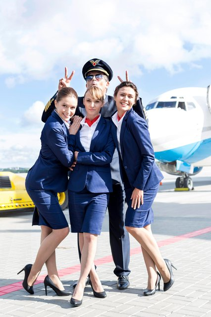 Stewardesses and pilot posing on airport runway. (Photo by Westend61/Getty Images)