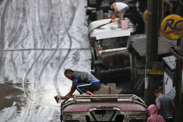 Residents clean ash from their vehicles from Taal Volcano's eruption Monday January 13, 2020, in Tagaytay, Cavite province, south of Manila, Philippines. (Photo by Aaron Favila/AP Photo)