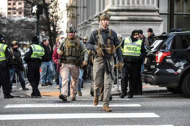 People who are part of an armed militia group walk near the Virginia State Capitol building to advocate for gun rights in Richmond, Virginia, January 20, 2020. Thousands of armed gun-rights activists filled the streets around Virginia's capitol building to protest a package of gun-control legislation making its way through the newly Democratic-controlled state legislature. (Photo by Stephanie Keith/Reuters)
