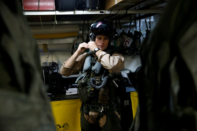 """Navy F/A-18 pilot Commander Higgins from the VFA-83 Squadron also known as the """"Rampagers"""" gets ready before a mission, on the USS Harry S. Truman aircraft carrier, in the eastern Mediterranean Sea, June 15, 2016. (Photo by Baz Ratner/Reuters)"""