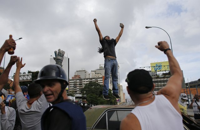 An anti-government demonstrator jumps on a car that later was burned during clashes with National Guards in Caracas, Venezuela, Thursday, July 20, 2017. Venezuelan President Nicolas Maduro and his opponents faced a crucial showdown Thursday as the country's opposition called for a 24-hour national strike. (Photo by Ariana Cubillos/AP Photo)