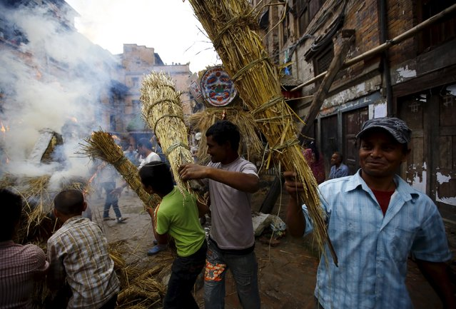 "People carry an effigy of the demon Ghantakarna, while another effigy of the demon is burnt to symbolize the destruction of evil, during the Ghantakarna festival in the ancient city of Bhaktapur, Nepal August 12, 2015. According to local folklore, the demon is believed to ""steal"" children and women from their homes and localities. (Photo by Navesh Chitrakar/Reuters)"