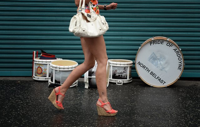 A female band supporter runs past a shop front on her way to watch the start of the annual 12th of July march in Belfast city centre on July 12, 2014 in Belfast, Northern Ireland. The parade's celebrate the protestant King William of Orange's victory over the catholic English King James II at the Battle of the Boyne in 1690. (Photo by Charles McQuillan/Getty Images)