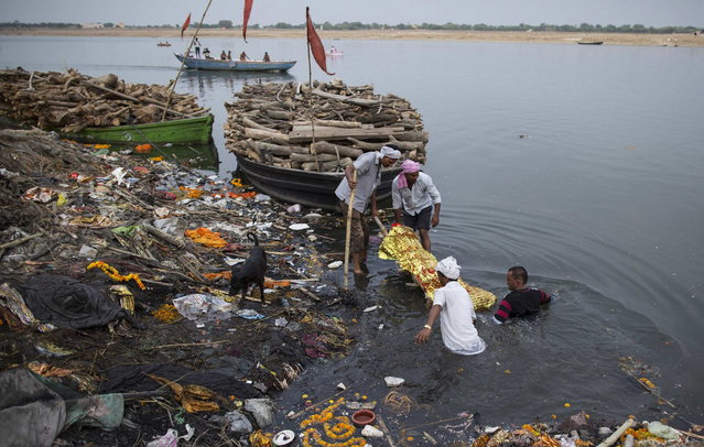 Relatives immerse a body in the river Ganges prior to cremation in Varanasi, in the northern Indian state of Uttar Pradesh, June 19, 2014. (Photo by Danish Siddiqui/Reuters)