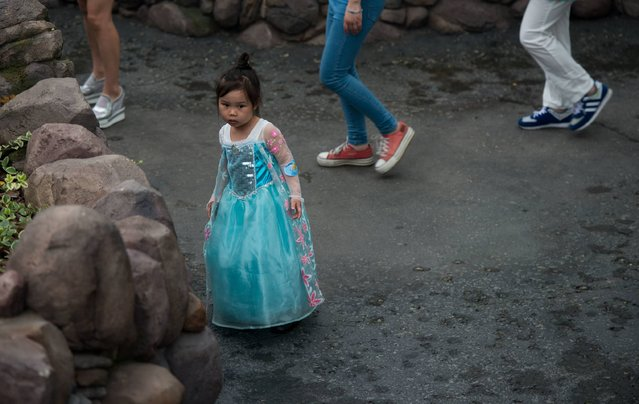 """A young girl in her princess outfit reacts to the sound of a dog in the """"Alice in Wonderland Maze"""" atraction on opening day at the Shanghai Disney Resort in Shanghai on June 16, 2016. Entertainment giant Disney opened a massive theme park in Shanghai on June 16, hoping to win over communist-ruled China's growing middle class with the ultimate US cultural export. (Photo by Johannes Eisele/AFP Photo)"""
