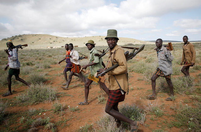 Turkana tribesmen walk with guns to protect their cattle from rival tribes near Baragoy, Kenya August 4, 2017. (Photo by Goran Tomasevic/Reuters)