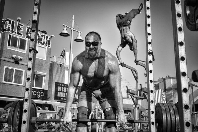 Honourable mention, people – Muscle Beach Gym. A weightlifter lifts a barbell loaded with heavy plates while a bodybuilder performs an aerial handstand at the Muscle Beach Gym in Venice Beach, California. (Photo by Dotan Saguy/National Geographic Travel Photographer of the Year Contest)