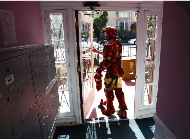 "In this Sunday, June 4, 2017 photo, wearing a $5,000 Iron Man costume, actor Paul Louis Harrell leaves his apartment building, in the Hollywood section of Los Angeles. ""I'm successful because I have the best costume on the block and it's the most expensive one on the block"", said Harrell. Longtime street performers like Harrell have concerns. They say business used to be more lucrative until the boulevard became overpopulated with costumed characters. What's worse, some look grungy, while others turn off tourists with aggressive demands for money. (Photo by Jae C. Hong/AP Photo)"