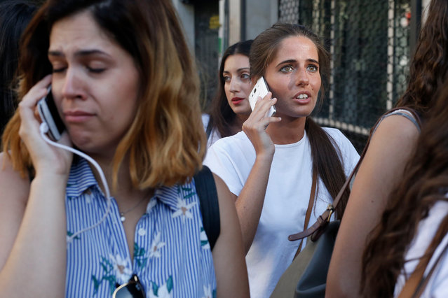 People phone to relatives or friends after a van ploughed into the crowd, killing one person and injuring several others on the Rambla in Barcelona on August 17, 2017. (Photo by Pau Barrena/AFP Photo)