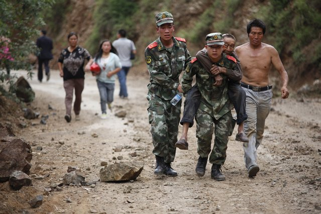 Chinese rescuers carry an injuried resident after an earthquake hit an area of Ludian county in Zhaotong in southwest China's Yunnan province on August 3, 2014. At least 150 people were killed and 1,300 injured after a strong earthquake hit southwest China's mountainous Yunnan province, state media said. The quake in Zhaotong prefecture, in the province's northeast, toppled buildings and left residents frantically searching for survivors beneath the rubble, images on social media showed. (Photo by AFP Photo)