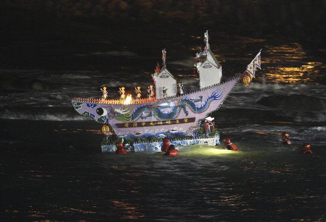 In this photo made early Sunday, Aug. 10, 2014, in Keelung, Taiwan, an elaborate model house is seen being guided into the ocean as an offering to wandering ghosts during the beginning of the Chinese folklore's mid-summer's Ghost Month Festival. (Photo by Chiang Ying-ying/AP Photo)