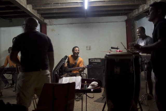 "Bass player Daniel Saias (C), 26, reacts during a rehearsal of the band ""Carlon y La Novena"" in downtown Havana, February 10, 2015. (Photo by Alexandre Meneghini/Reuters)"