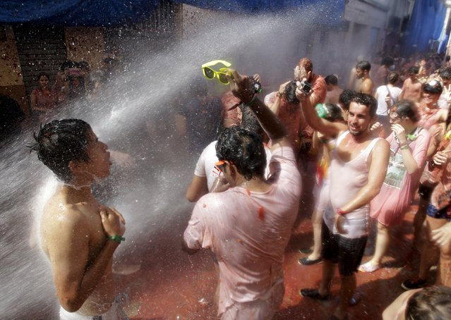 """Revelers are sprayed with water after the annual """"Tomatina"""" (tomato fight) in Bunol, near Valencia, Spain, August 26, 2015. (Photo by Heino Kalis/Reuters)"""