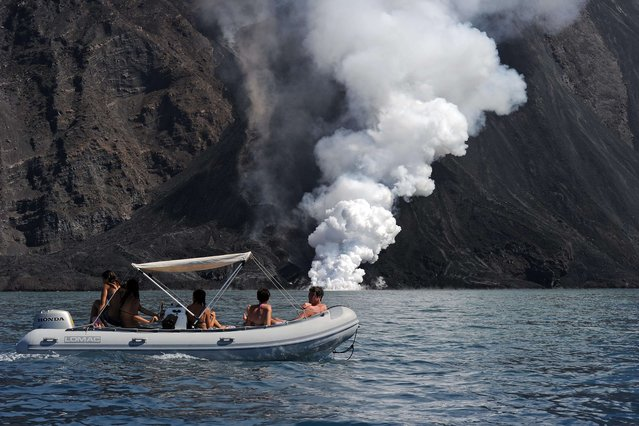 People sail on a boat as lava from the Stromboli volcano flows into the sea, on August 9, 2014. Stromboli, one of Europe's most active volcano, is part of the seven-island Eolian Archipelago just off Sicily in southern Italy. (Photo by Giovanni Isolino/AFP Photo)