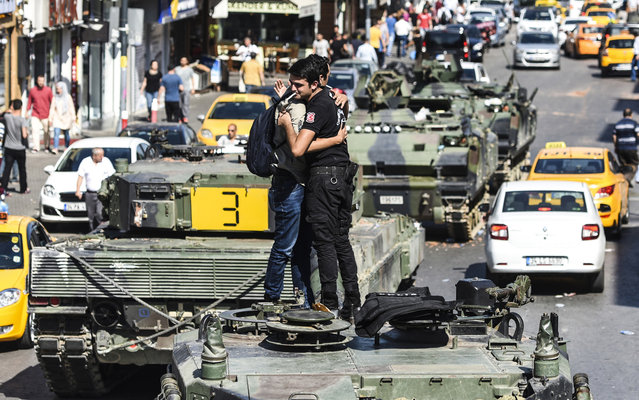 """Turkish police officer (R) embrace a man on a tank after the military position was taken over at the Anatolian side at Uskudar in Istanbul on July 16, 2016. President Recep Tayyip Erdogan urged Turks to remain on the streets on July 16, 2016, as his forces regained control after a spectacular coup bid by discontented soldiers that claimed more than 250 lives. Describing the attempted coup as a """"black stain"""" on Turkey's democracy, Yildirim said that 161 people had been killed in the night of violence and 1,440 wounded. (Photo by Bulent Kilic/AFP Photo)"""