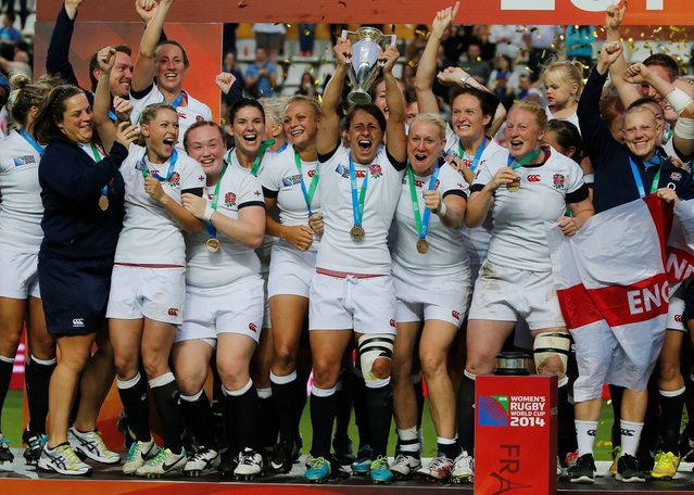 England's captain Katy McLean, holds the trophy as she celebrates with her teammates, after defeating Canada 21-9, during the final match of the Women's Rugby World Cup 2014, at Jean Bouin stadium, in Paris, Sunday, August 17, 2014. (Photo by Michel Euler/AP Photo)