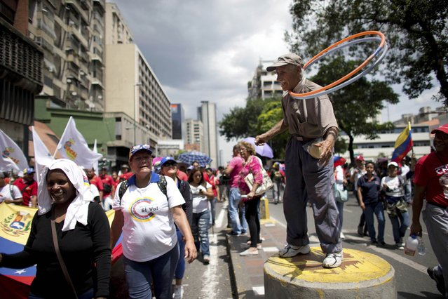 """In this September 19, 2017 photo, government supporters march past a street performer working hula hoops around his neck, during an anti-imperialist demonstration, in Caracas, Venezuela. In his debut address to the U.N. General Assembly, U.S. President Donald Trump says the socialist government in Venezuela has brought a once-thriving nation to the """"brink of collapse"""". Trump accused its President Nicolas Maduro of stealing power from elected representatives to preserve his """"disastrous rule"""". (Photo by Ariana Cubillos/AP Photo)"""