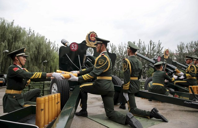 Paramilitary policemen and members of a gun salute team prepare to fire cannons during a training session for the upcoming military parade to mark the 70th anniversary of the end of the World War Two, at a military base in Beijing, China, September 1, 2015. (Photo by Reuters/Stringer)