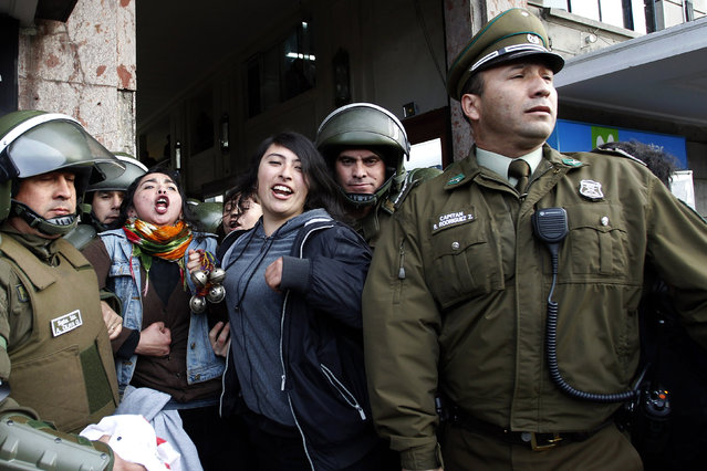 Two young people shout slogans while being detained by police during a demonstration in Concepcion, southern Chile, 25 September 2017. At least 30 activists were detained today after a protest that took place outside the cathedral of Concepcion, southern Chile, in support of four Mapuche activists who have been on hunger strike for 110 days. (Photo by Dragomir Yankovic/EPA/EFE)