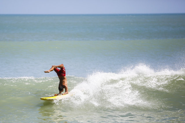 Tourists surf at a beach in Kuta, Bali, Indonesia, August 13, 2014. In the first half of 2014 the number of tourists visiting Indonesia increased by about 9.6 percent to 4.55 million from 4.15 million visitor in the same period last year. Indonesia may achieve about 14 percent growth in foreign tourist arrivals in 2014, according to the World Travel & Tourism Council (WTTC). (Photo by Made Nagi/EPA)