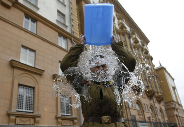 """Alexei Didenko, a deputy for the Russian State Duma, dumps a bucket of cold water on himself in front of the American embassy in Moscow, September 3, 2014. Didenko said he was performing the ice bucket challenge not only to raise awareness for ALS (Amyotrophic Lateral Sclerosis) research, but also to protest against new U.S. Ambassador to Russia John Tefft, and what Didenko calls """"anti-Russian American propaganda"""". (Photo by Maxim Zmeyev/Reuters)"""