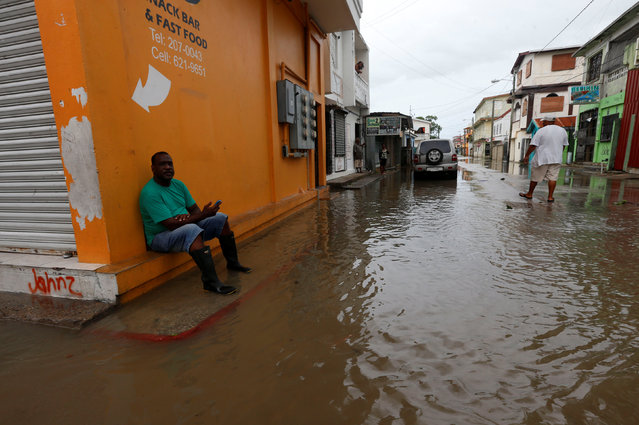 A man sits at a flooded street, after Hurricane Earl hit, in Belize City, Belize August 4, 2016. (Photo by Henry Romero/Reuters)