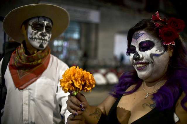 """People fancy dressed as """"Catrina"""" take part in the """"Catrinas Parade"""" along Reforma Avenue, in Mexico City on October 22, 2017. (Photo by Ronaldo Schemidt/AFP Photo)"""