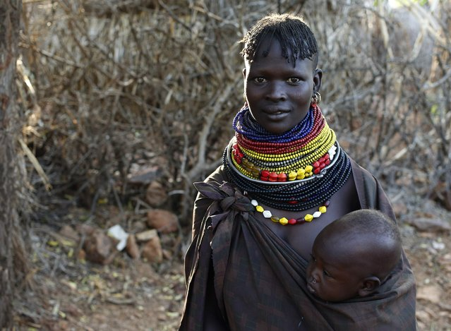 A Turkana woman carrying a child stands by a hut in Napak village in northwestern Kenya inside the Turkana region of the Ilemy Triangle September 25, 2014. (Photo by Goran Tomasevic/Reuters)