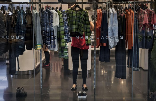 A Chinese store clerk arranges clothes at a foreign boutique at a shopping mall on September 12, 2014 in Beijing, China. (Photo by Kevin Frayer/Getty Images)